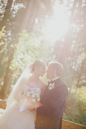 bride and groom in a forest with sunlight shining through the trees