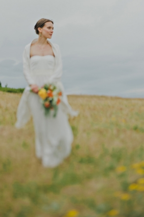 bride holding orange and yellow bouquet