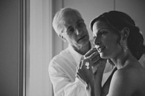 bride puts on earring with help of her father
