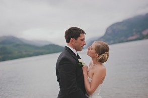 bride and groom embrace near a lake