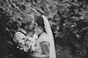 bride and groom kiss in a forest