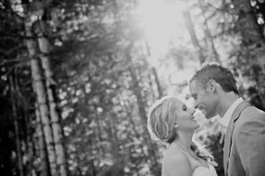 bride and groom stand nose to nose in the forest