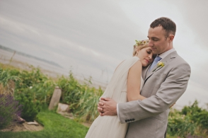 bride and groom hug next to a beach