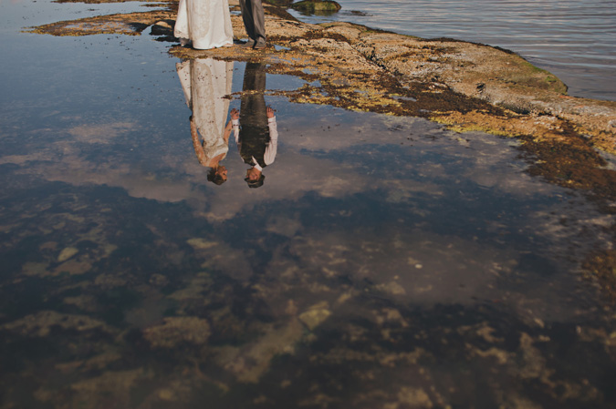 a reflection of a bride & groom in a tidal pool on hornby island, bc