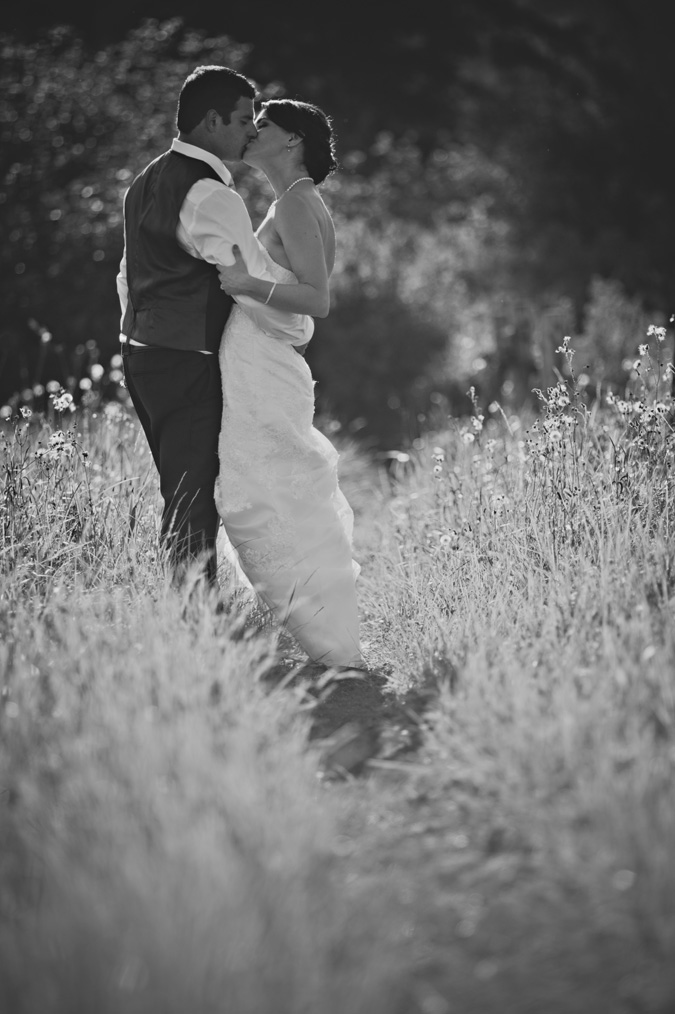 intimate portrait of a bride & groom kissing in the tall grass at salmon point, campbell river, vancouver island, bc