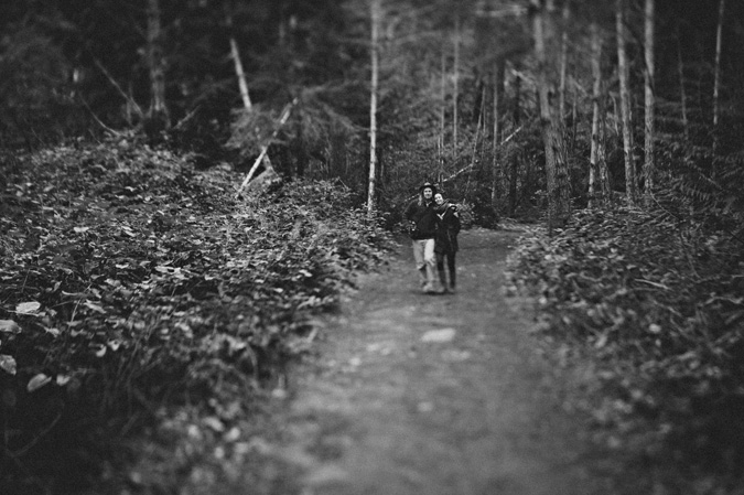 a couple walking arm in arm in the forest