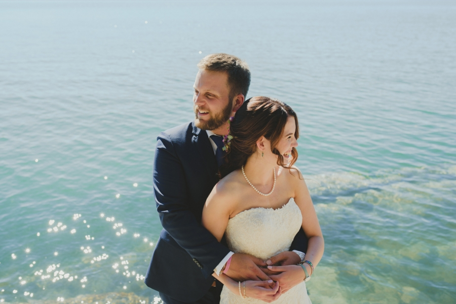 intimate bodega ridge wedding - galiano island - couple hugging in front of sparkling ocean