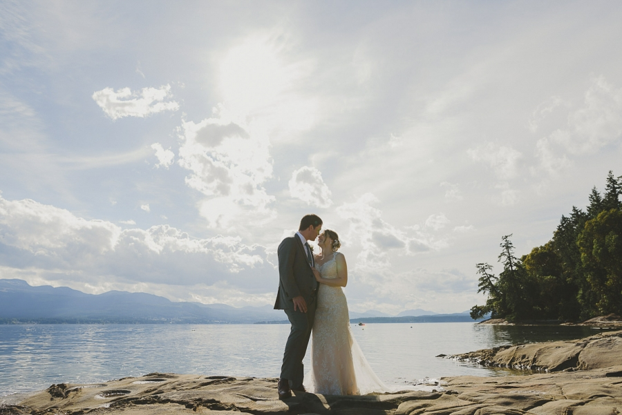 overbury resort thetis island wedding-couple kissing with the ocean & big sunset sky behind them