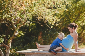 young pregnant woman sitting on a picnic bench with her young son hugging her pregnant belly-hornby island lifestyle maternity session