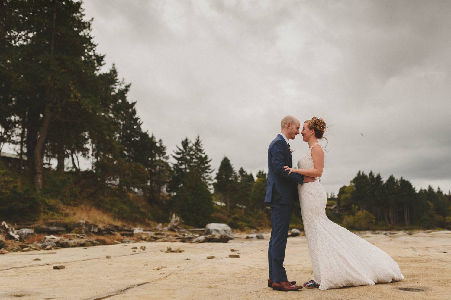 bride & groom on the beach with wind blowing