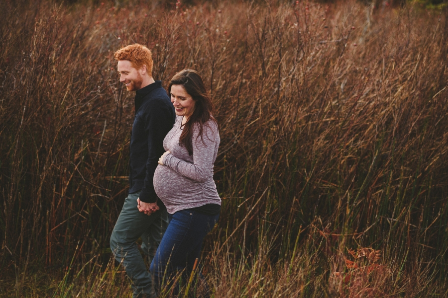 pregnant couple walking in grass hornby island maternity session