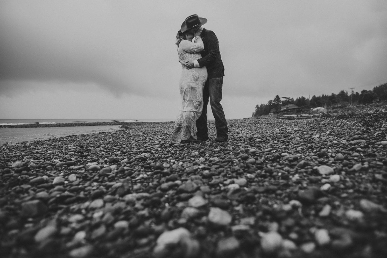 bride & groom kissing on a rainy day beach