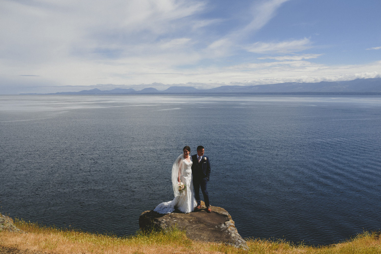 bride & groom at the edge of a cliffe overlooking the ocean
