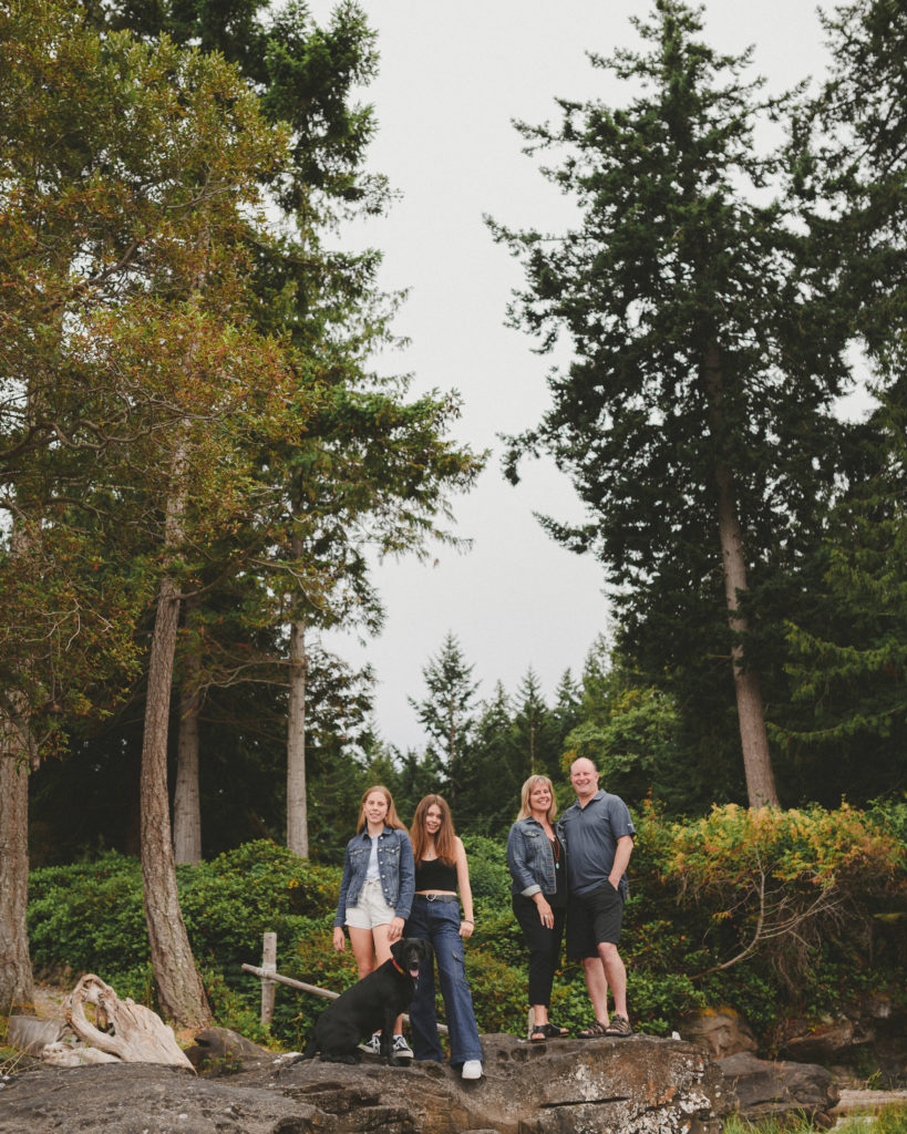 family standing in front of tall trees on hornby island