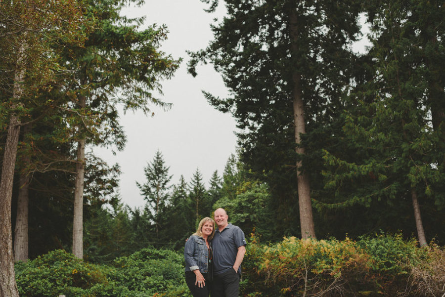 couple hugging in front of tall trees on hornby island