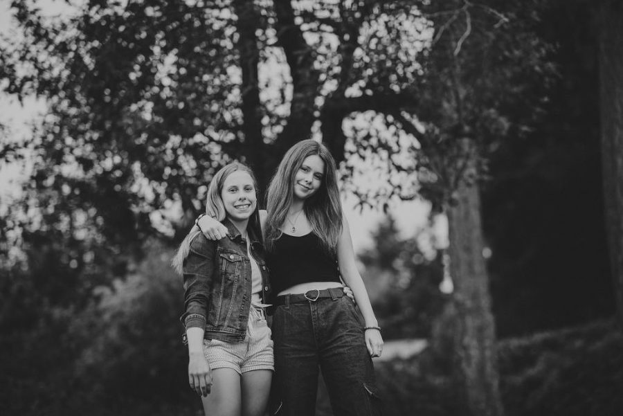 black & white photo of young sisters smiling in front of trees