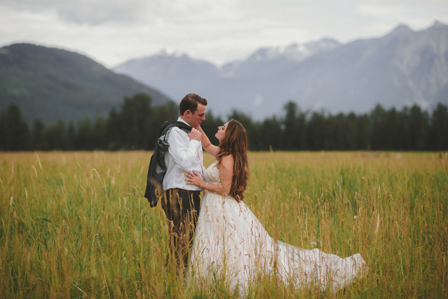 bride & groom in a field with the mountains behind them - riverlands red barn wedding