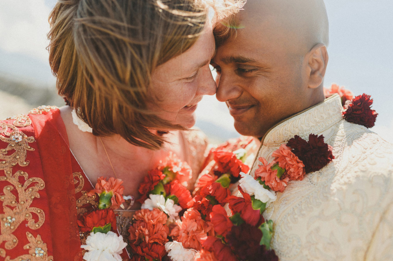 close up of mixed race couple with colourful garlands on their wedding day