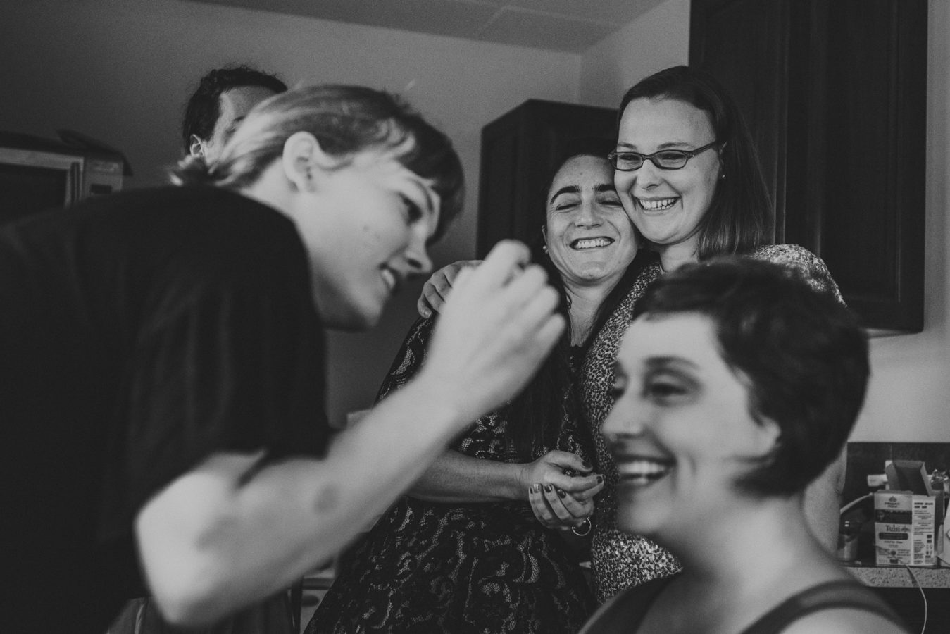 two lgbtq guests hugging and laughing while their friend gets make up done for her wedding