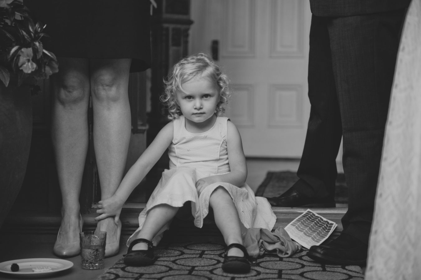 young girl in a dress sitting amongst adult legs holding her mother's ankle at a wedding
