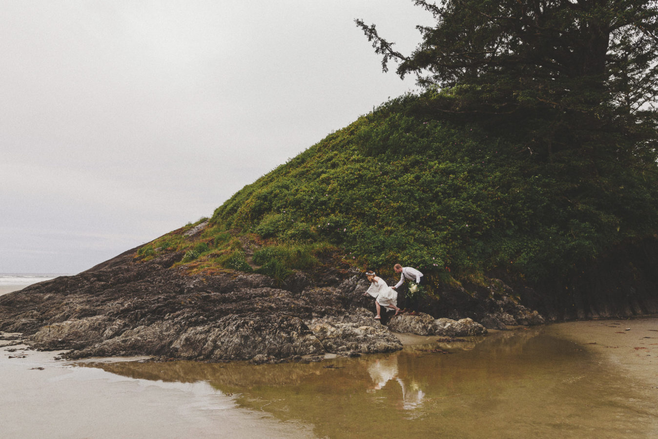 wedding couple climbing on rocks with reflection in the water below