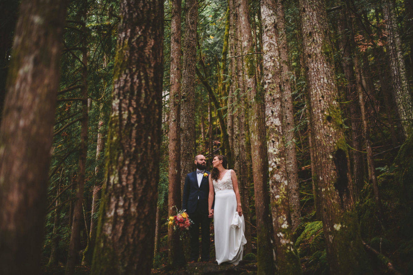 bride and groom holding hands and looking at each other amongst tall trees in the forest
