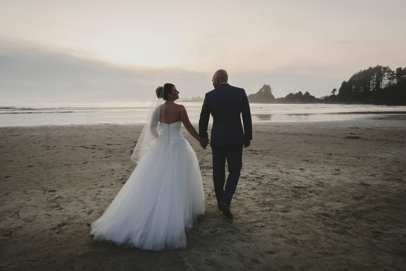 wedding couple holding hands and walking on the sunset beach in tofino