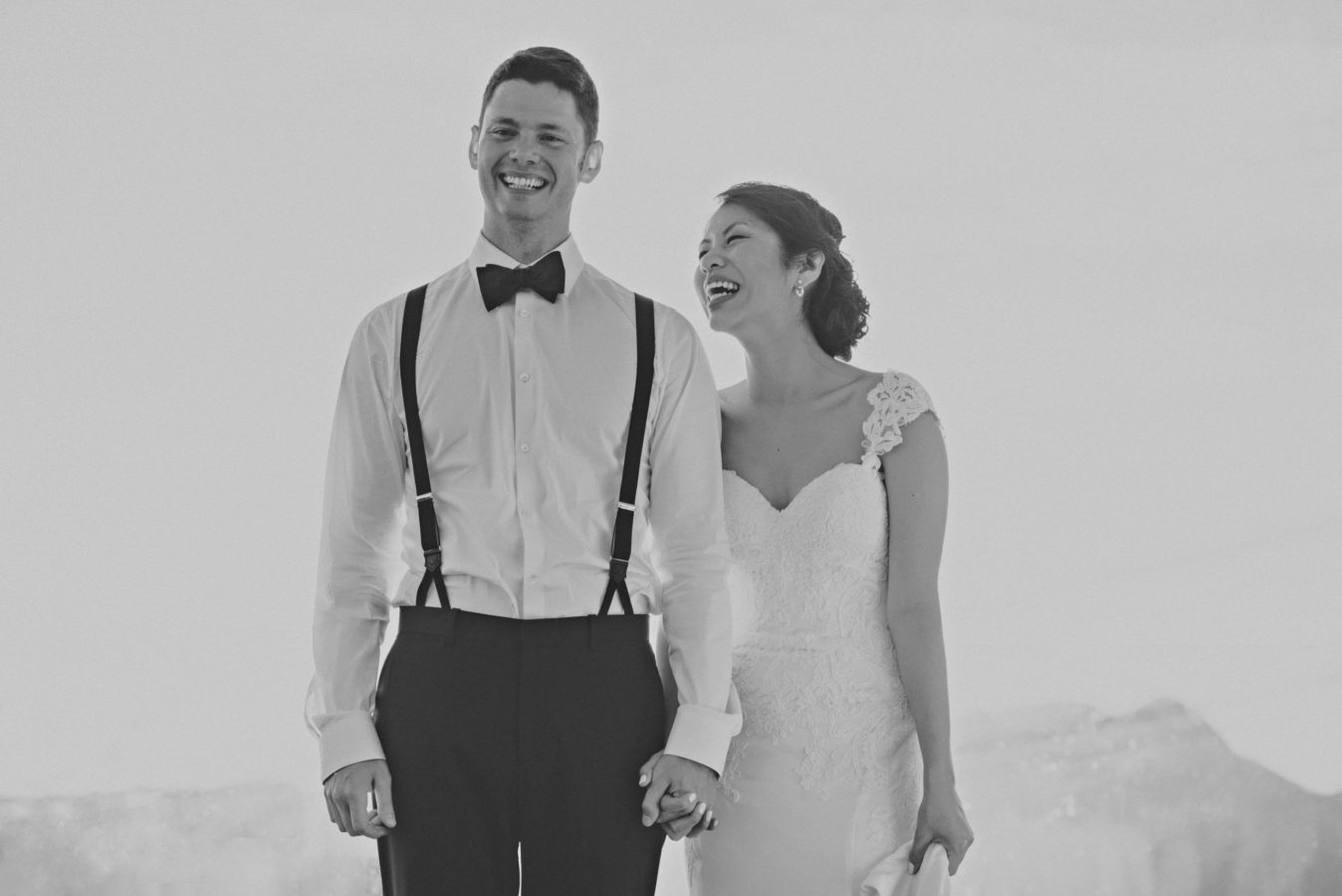 mixed race wedding couple holding hands and laughing