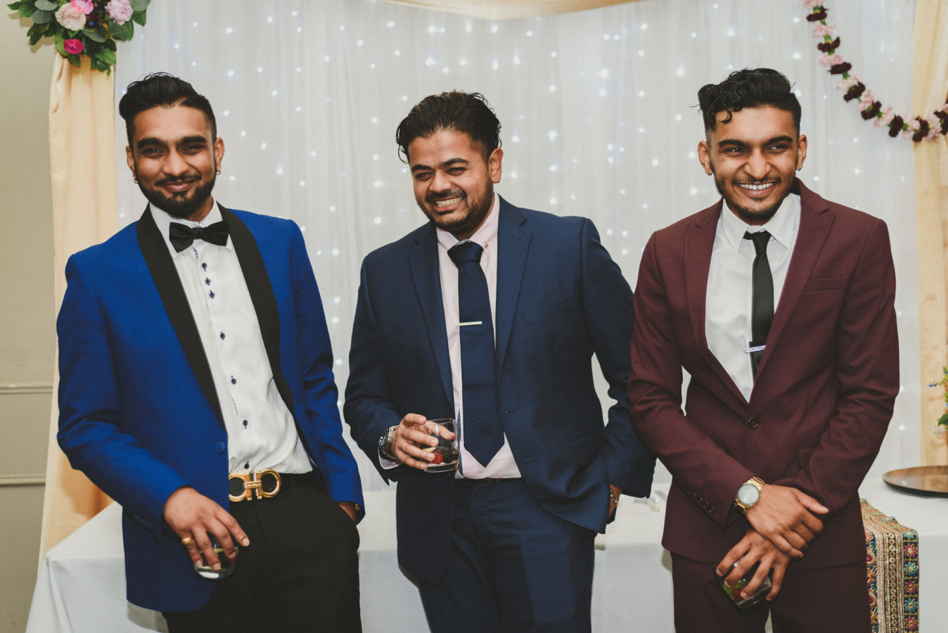 three well dressed men laughing at a wedding