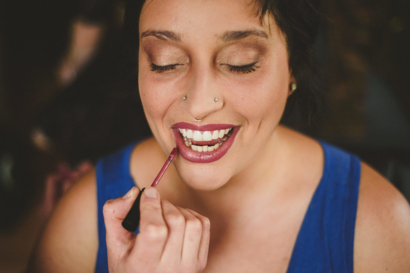 close up of a bride smiling while getting her lipstick applied on her wedding day