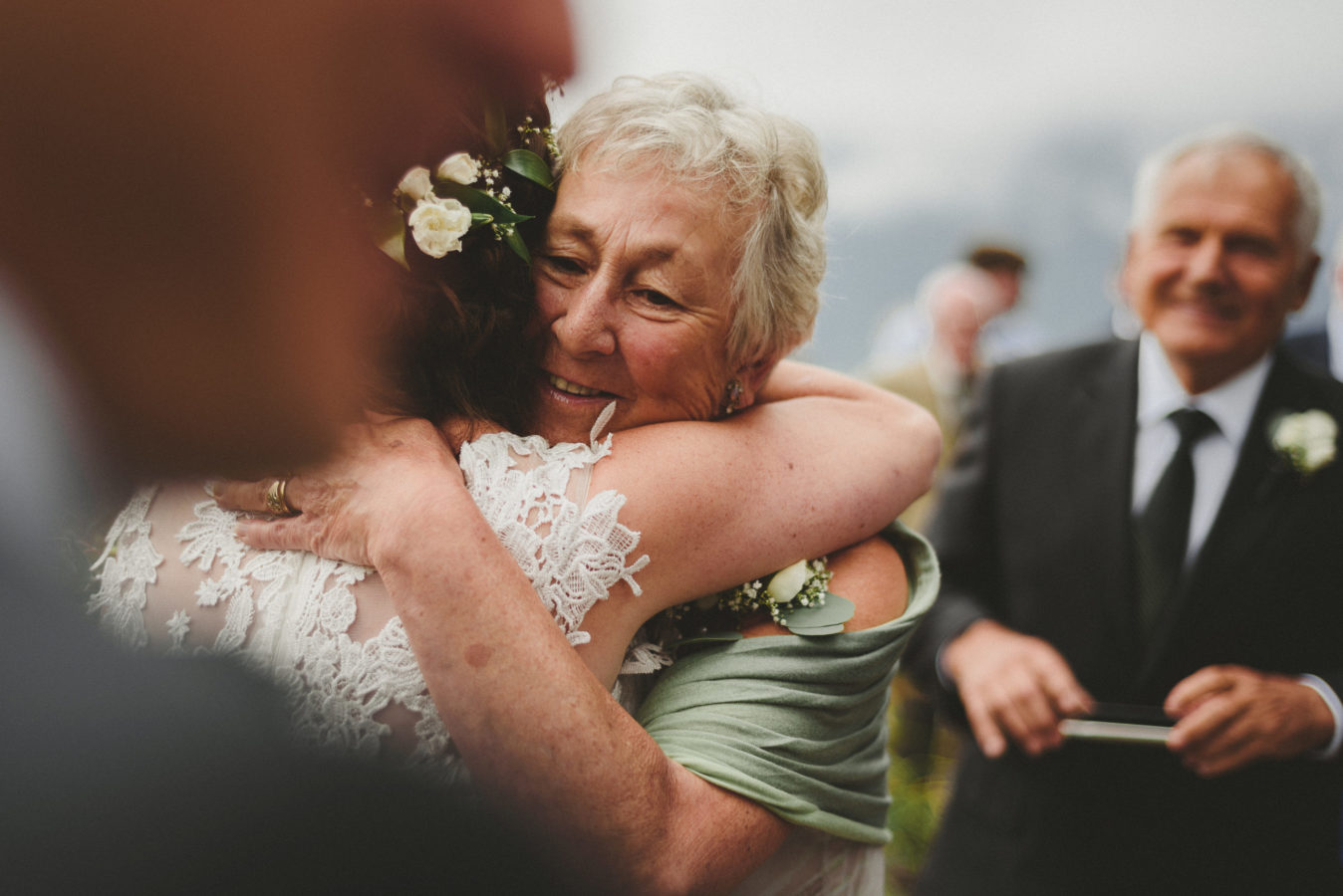 face of an older woman emotionally smiling as she hugs a bride on her wedding day