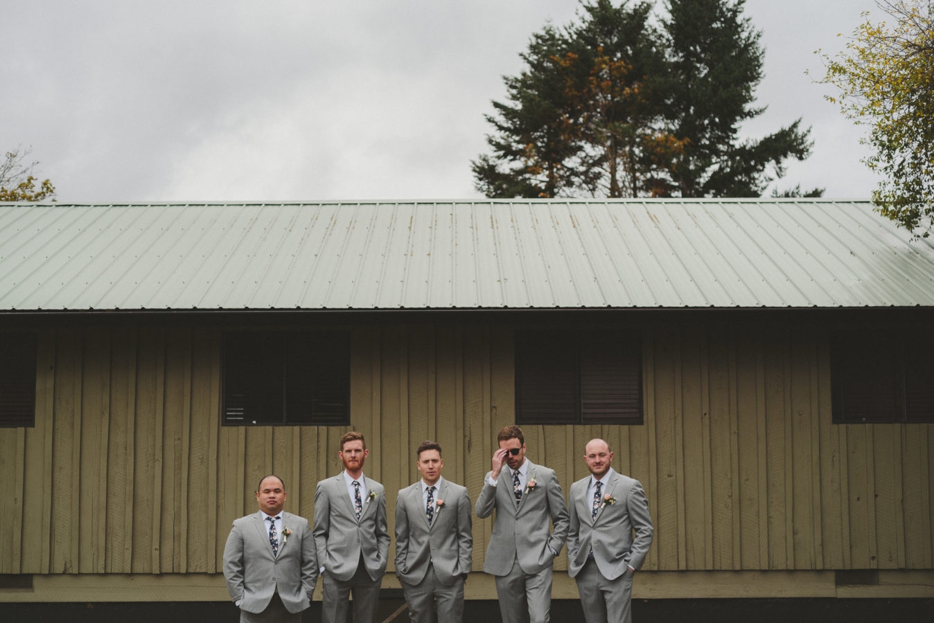 five groomsmen standing and looking at the camera against a rustic cabin