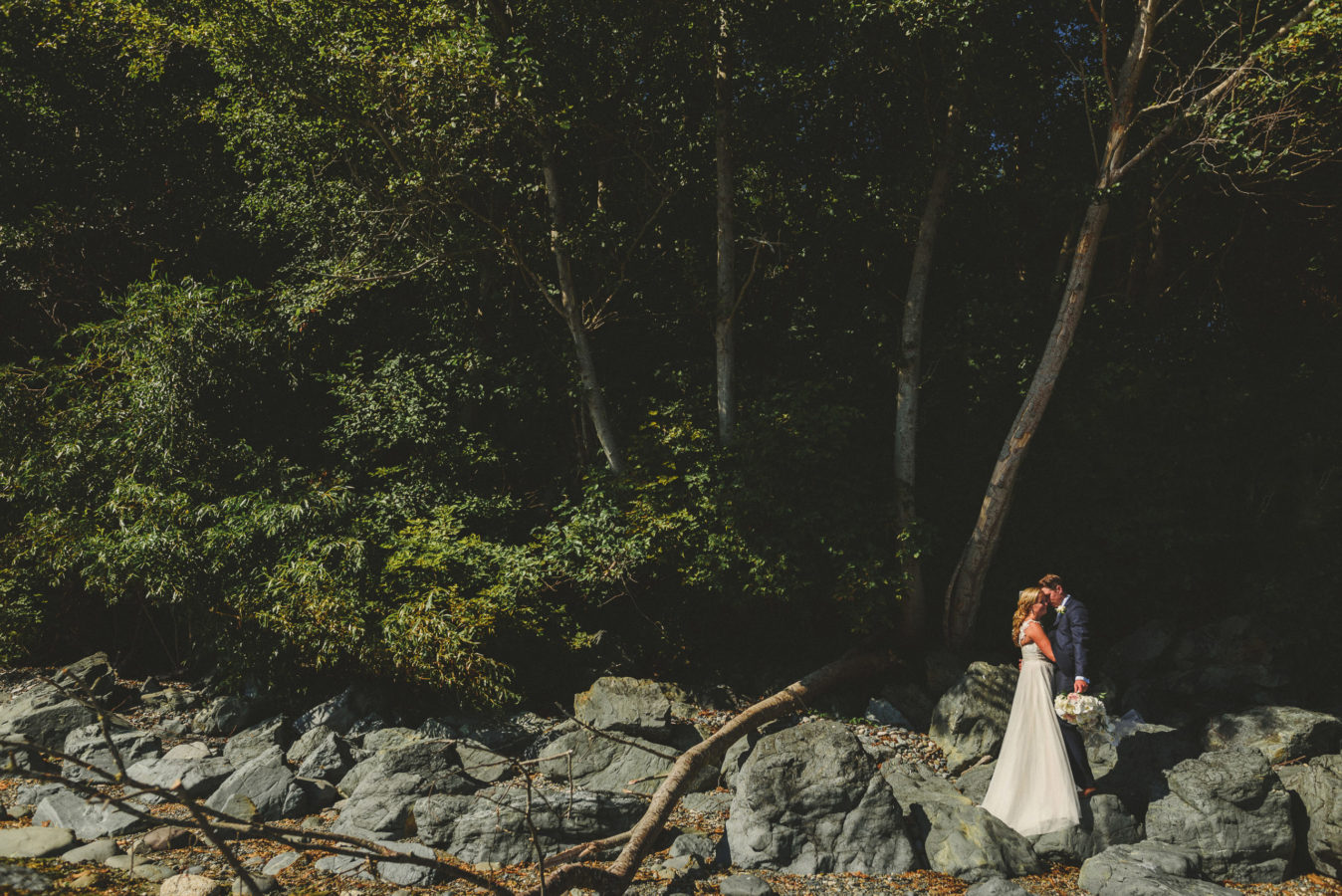 bride and groom kissing at the edge of a beach with tall trees behind them