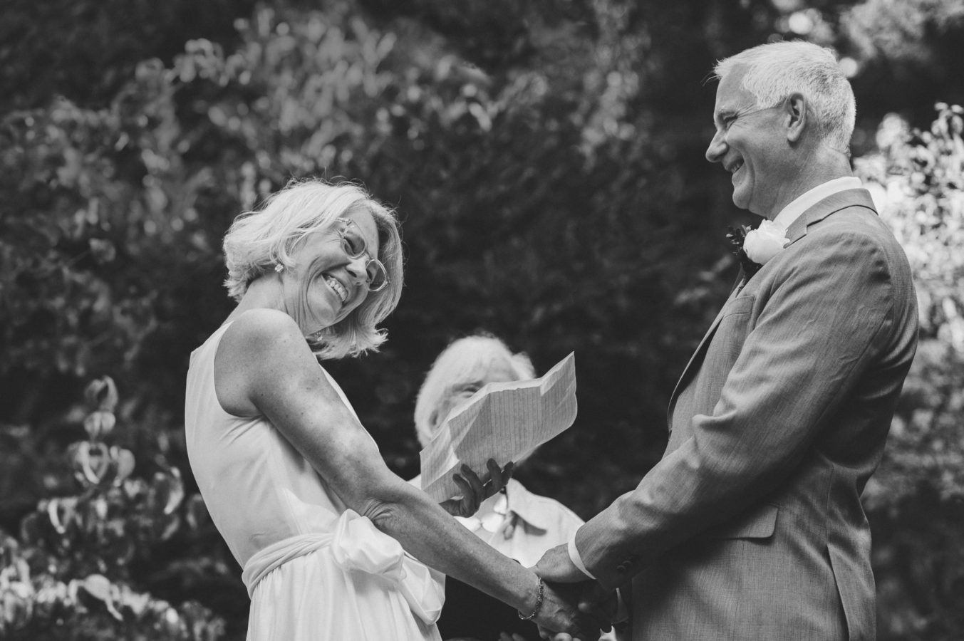 older bride and groom laughing during their wedding vows