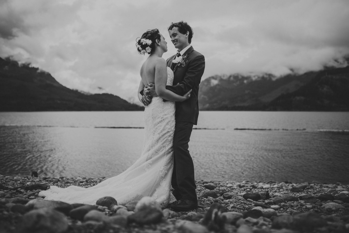 young bride and groom embracing in front of a lake & mountains on their wedding day