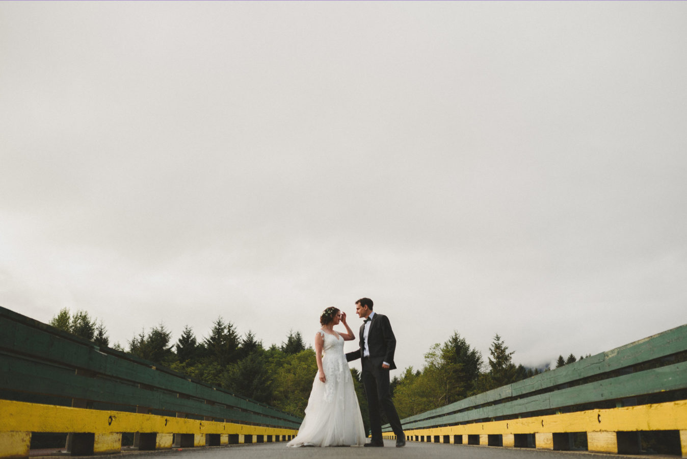bride and groom on a bridge looking at one another