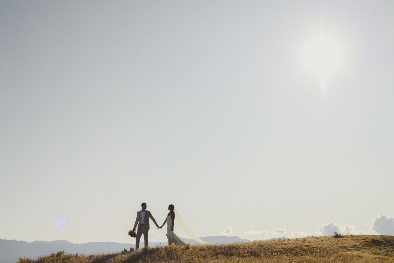 bride and groom walking along grassy cliffs with big sky behind them