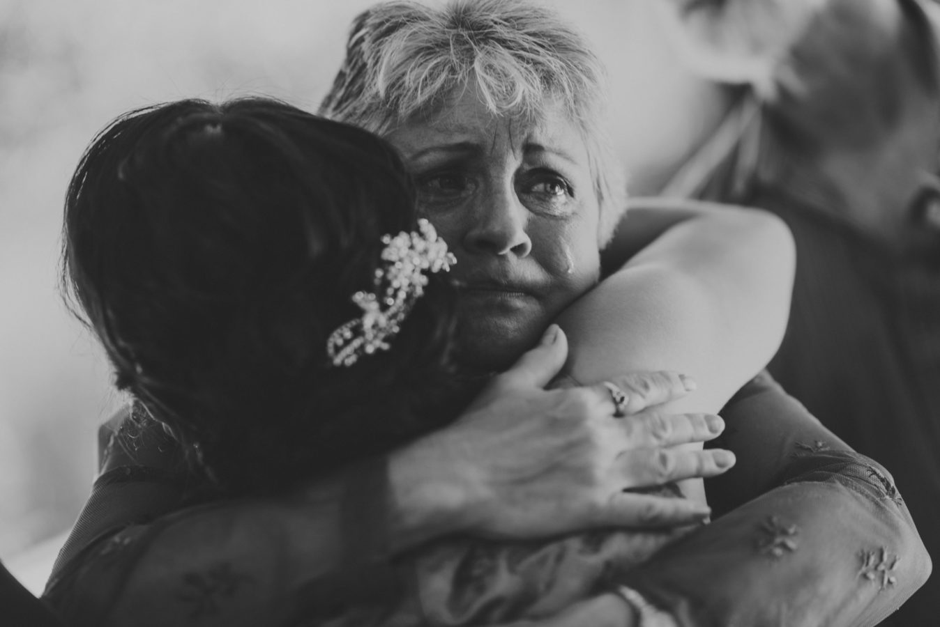 close up of a woman's teary face as she hugs a bride on her wedding day