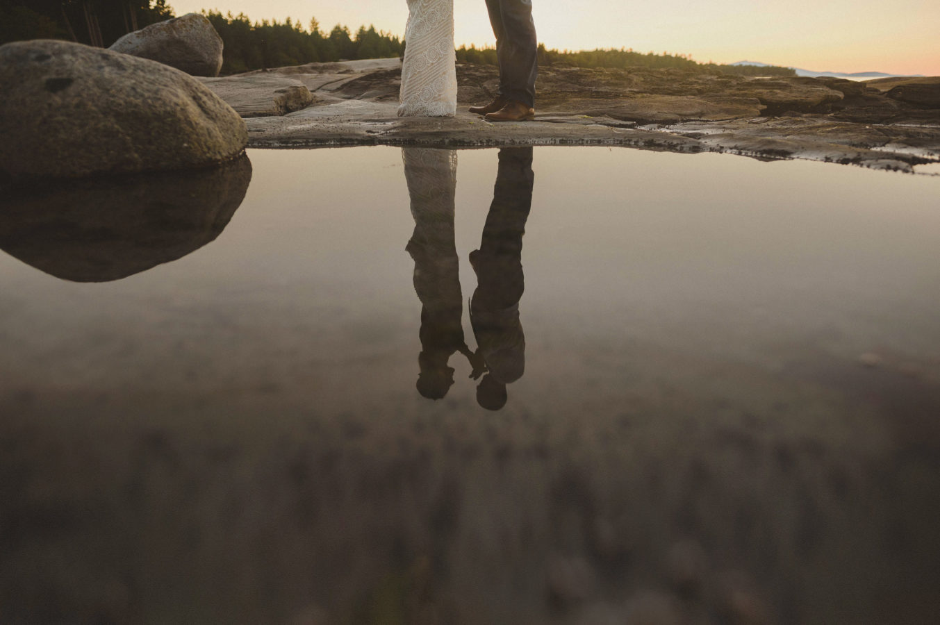 reflection of bride and groom in still water in a tidal pool