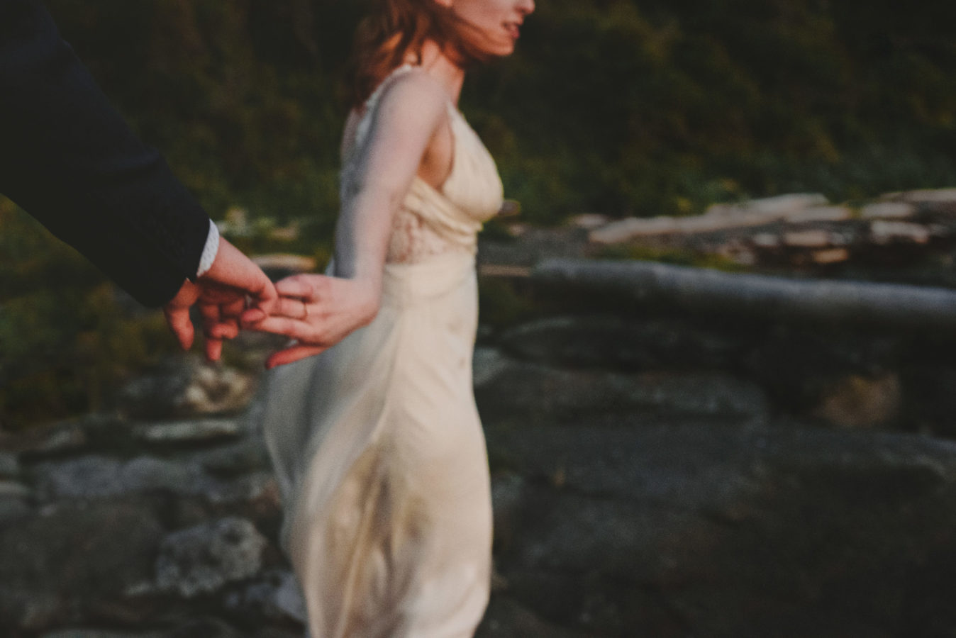 out of focus photo of a bride reaching back and holding her groom's hand walking along a beach after sunset
