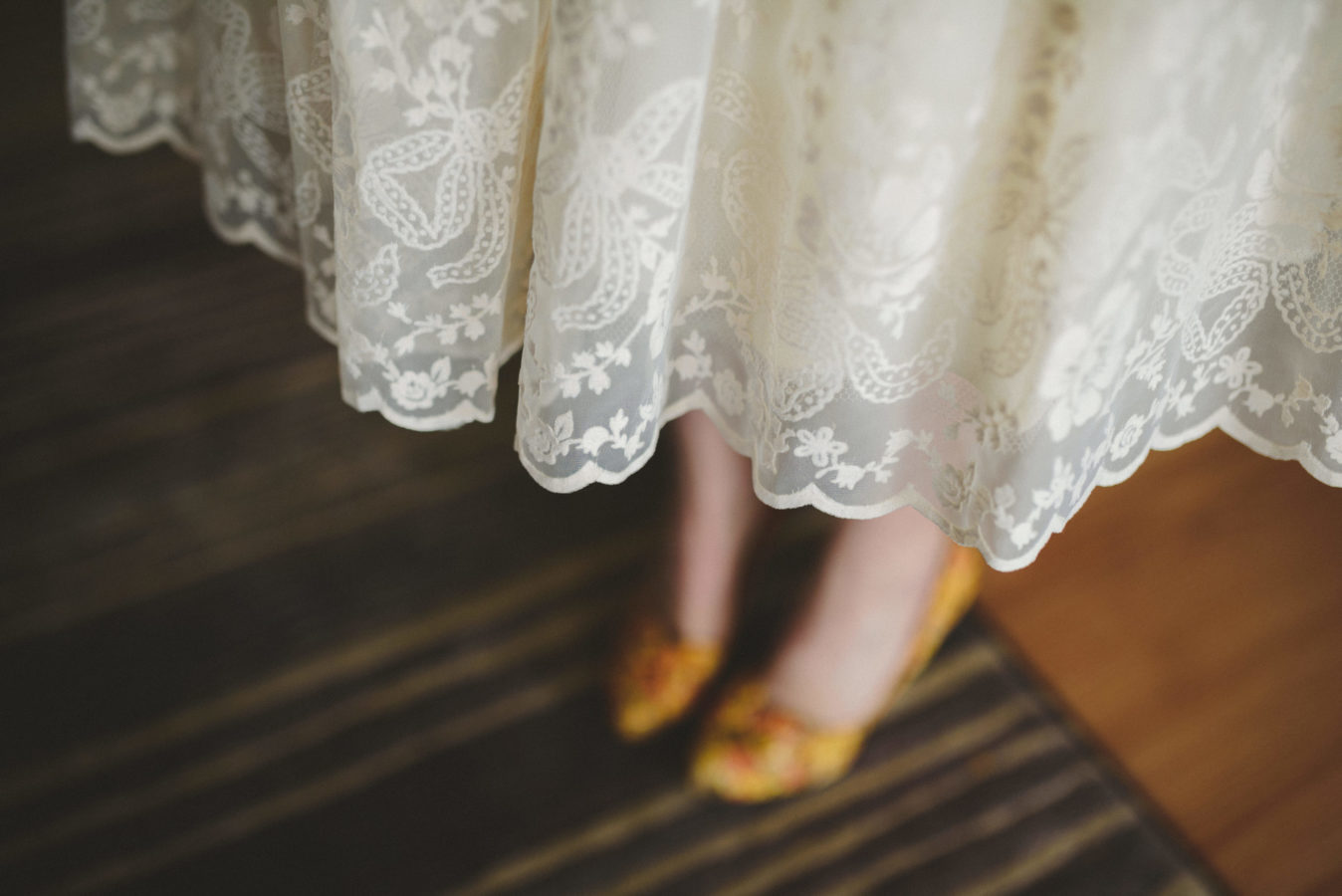 looking down on the lacy hem of a brides wedding dress with her yellow shoes underneath