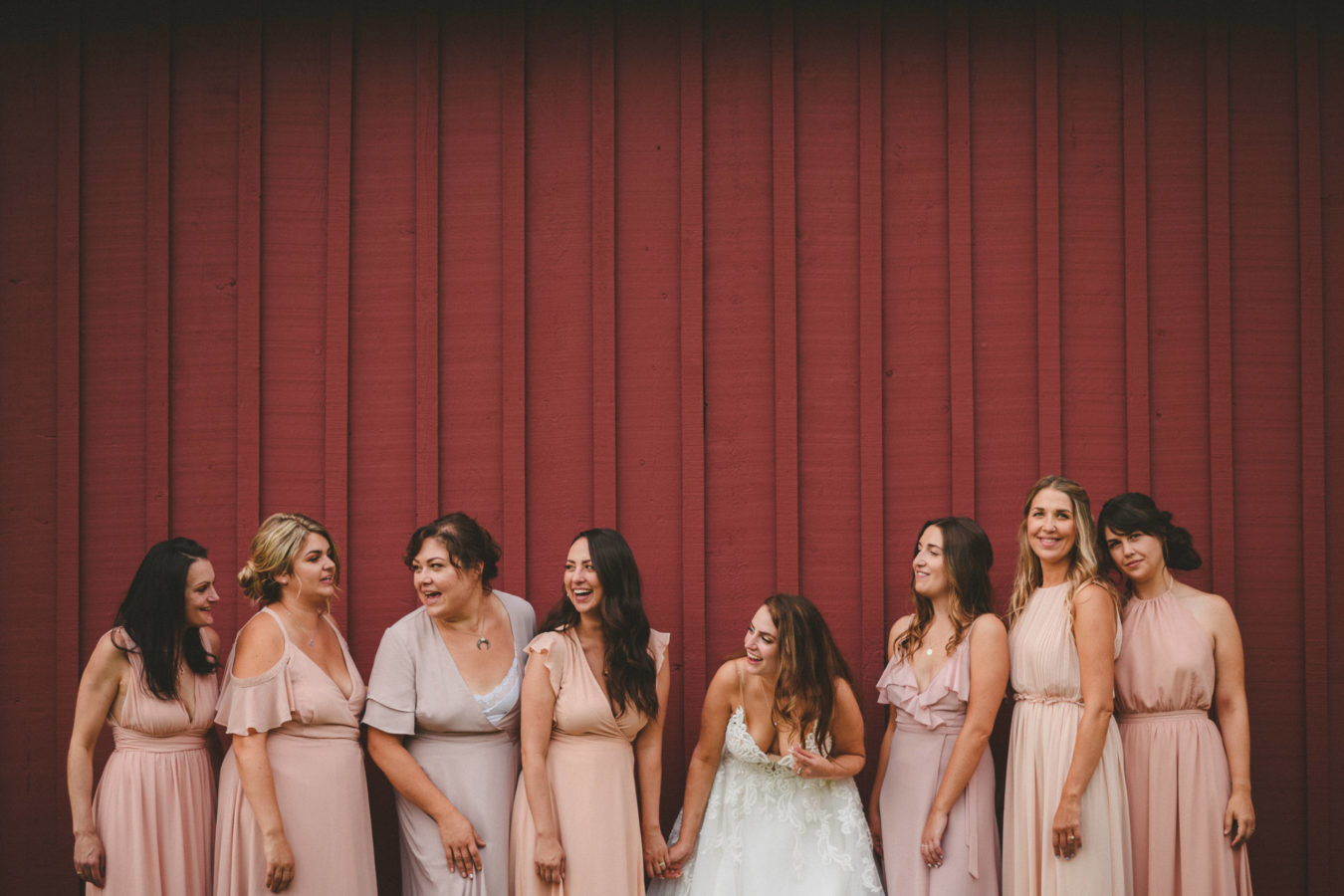 bride and bridesmaids laughing while leaning up against the red wall of a large barn