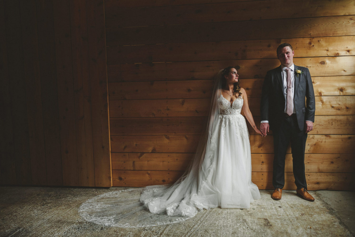 bride and groom holding hands in a barn with light coming in from the doors beside them