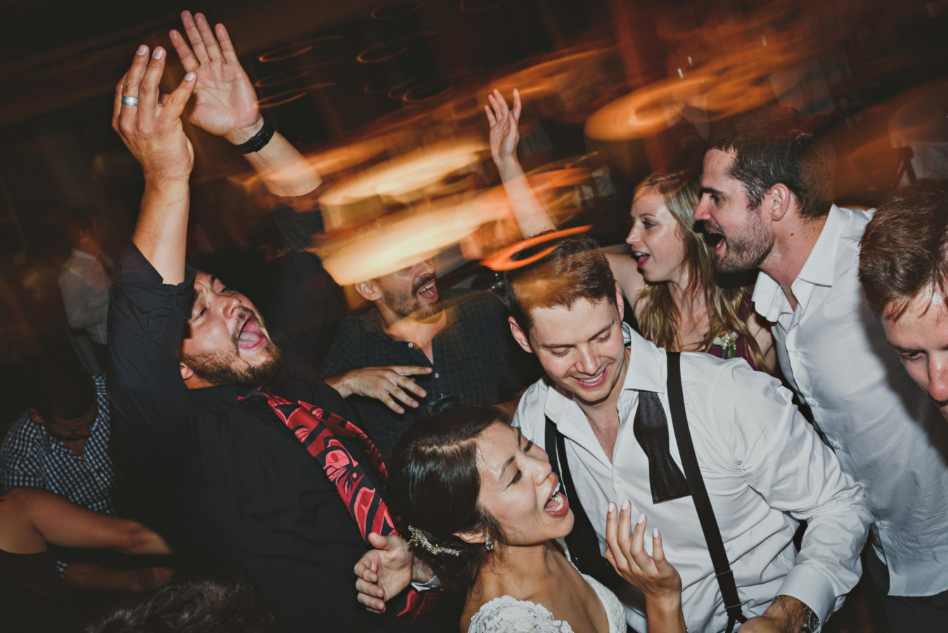 mixed race couple and friends laughing and partying on the dance floor