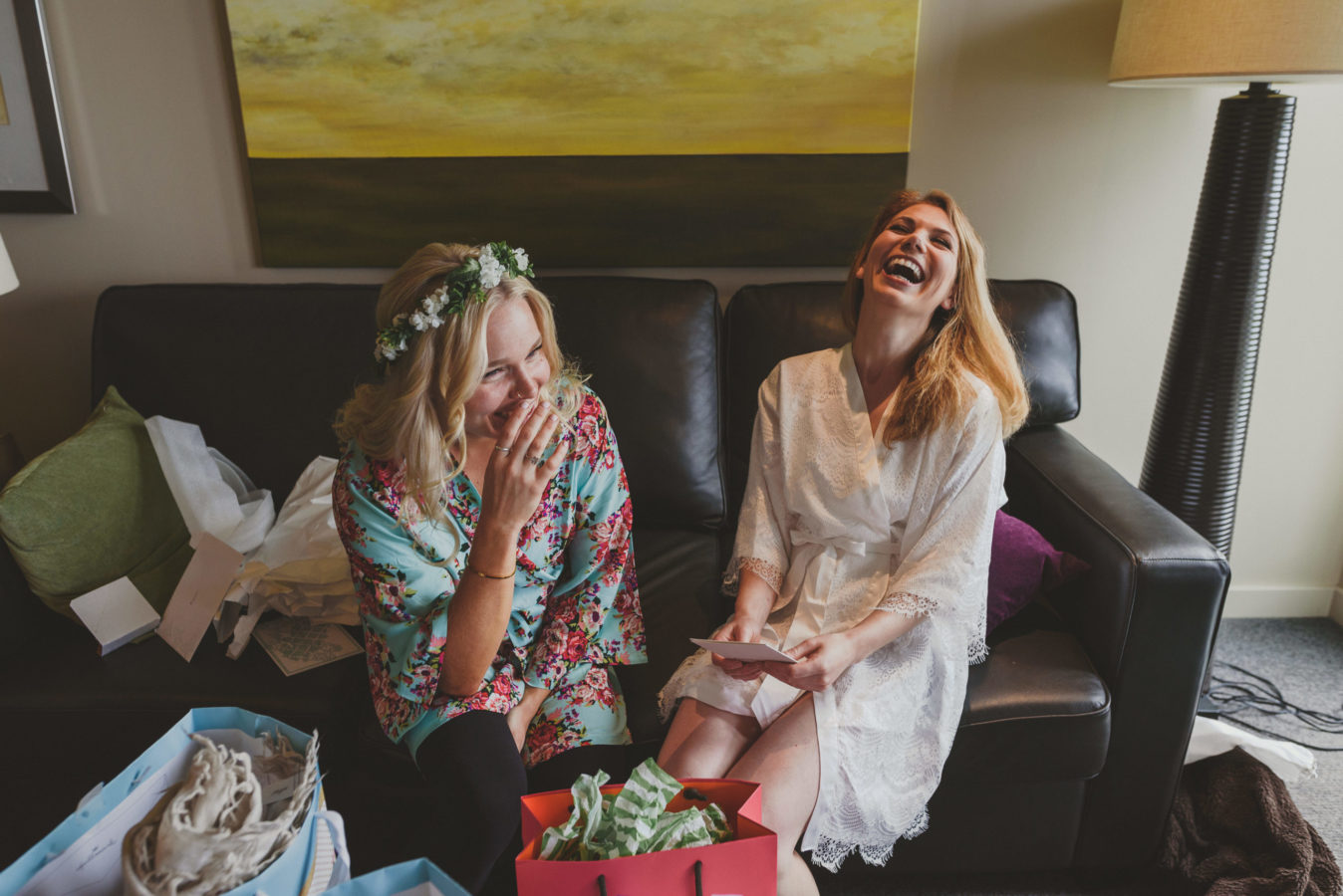 bride and bridesmaid in house coats laughing on a couch while getting ready
