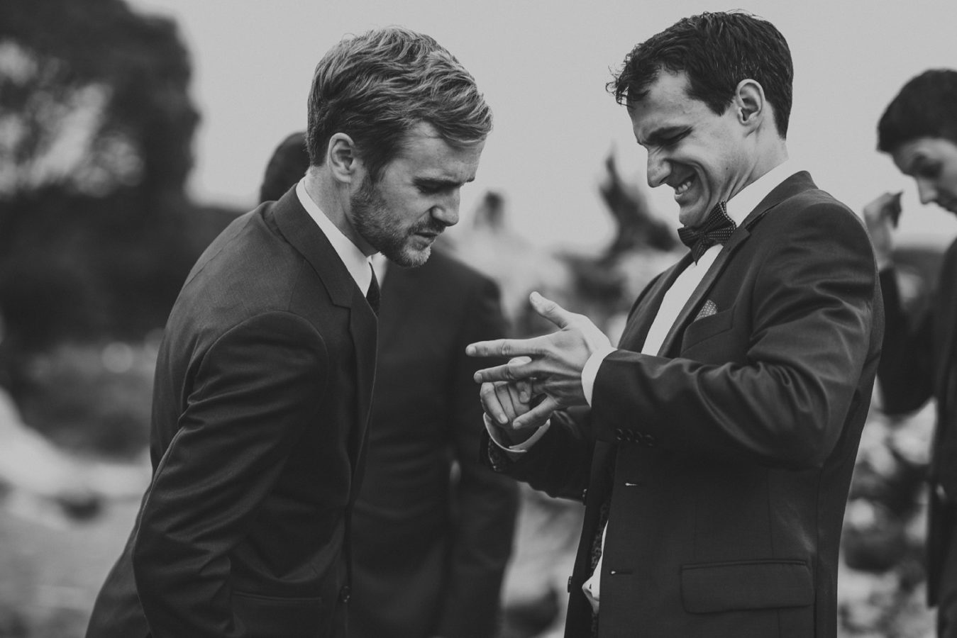 groom trying to pull off his wedding ring to show his friend but it's stuck