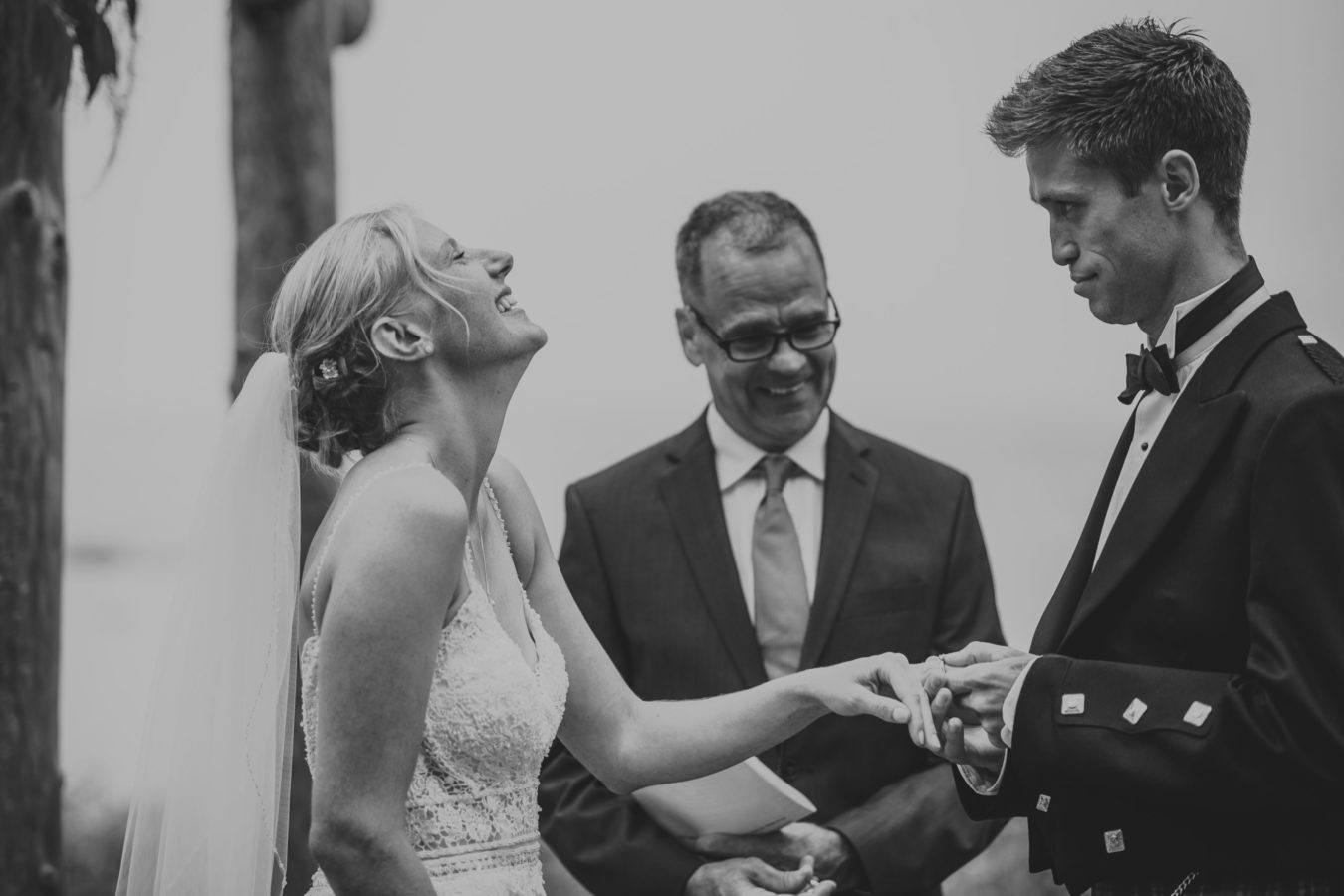 bride throwing her head back laughing while her groom tries to put on her ring during their wedding ceremony