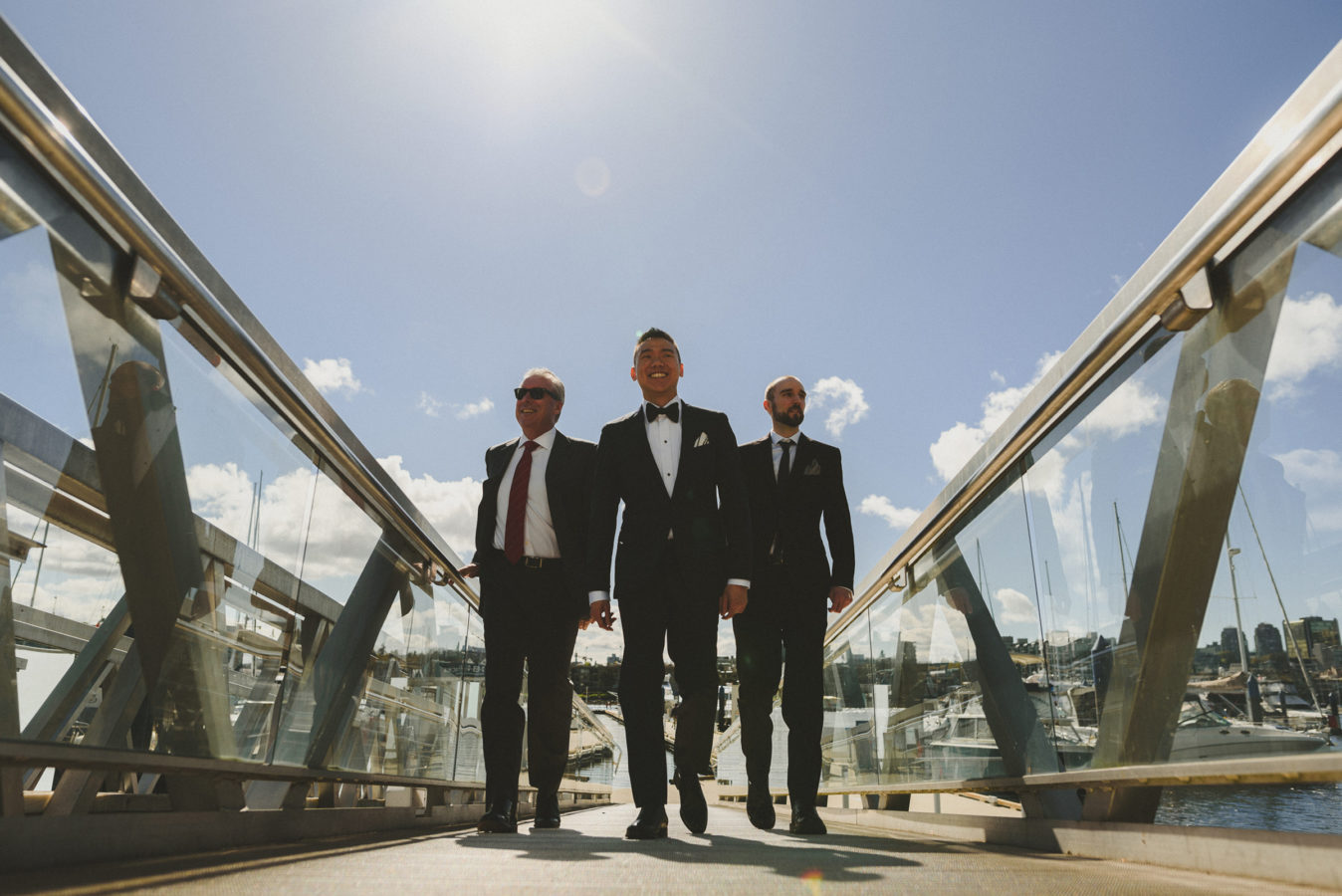 groom and two groomsmen walking up a dock with the sun & blue sky behind them