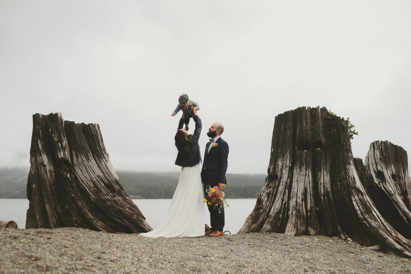 bride and groom on the beach by two huge stumps while bride gently tosses their toddler in the air above her