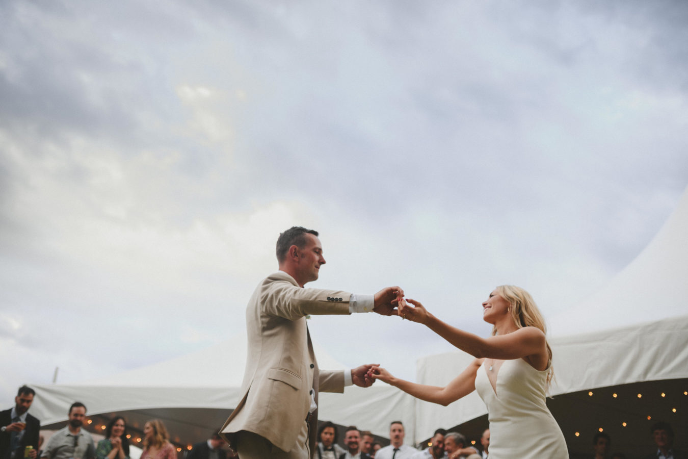 bride and groom dancing with guests looking on & white tents in the background